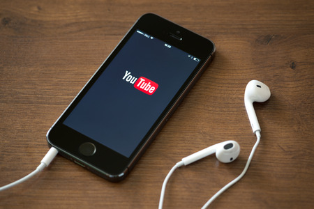 KIEV, UKRAINE - JUNE 05, 2014: Brand new Apple iPhone 5S with YouTube application service on the screen lying on a desk with headphones. YouTube is the worlds most popular online video-sharing website that founded in February 14, 2005