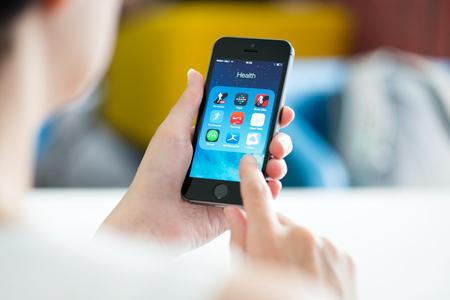 landline: KIEV, Ucraina - 21 Maggio 2014: Donna che osserva in materia di salute e di applicazione di fitness come Runtastic, FitBit, RunKeeper, Partenze, Road Bike, Nike Running e altre applicazioni su un nuovo marchio nero Apple iPhone 5S.