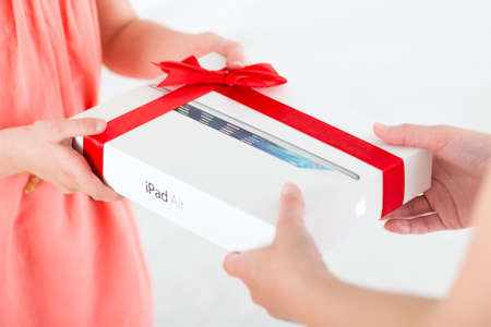 KIEV, UKRAINE - MAY 30, 2014: Mother gives her daughter a birthday present — brand new Apple iPad Air in a festive packaging. Apple iPad Air developed by Apple inc. and was released on November 1, 2013. Stock Photo - 28936425
