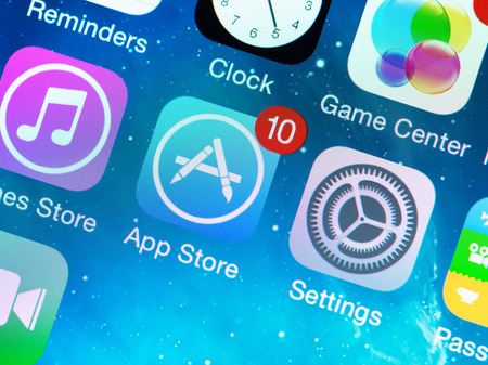 apple: KIEV, UKRAINE - JUNE 12, 2014: A close-up photo of Apple iPhone 5s start screen with application icons, includes App Store, Settings, Clock, Game Center and others. App Store is a digital distribution service for mobile apps on iOS platform, developed by
