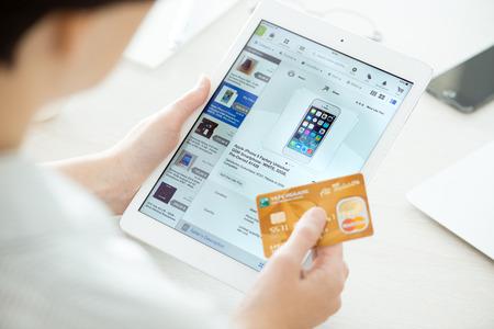 키예프, 우크라이나 - 2014년 6월 27일는 : 사람의 신용 카드를 들고와 새로운 애플 아이 패드 에어 이베이 응용 프로그램과 새로운 애플 아이폰 5를 구입 에디토리얼
