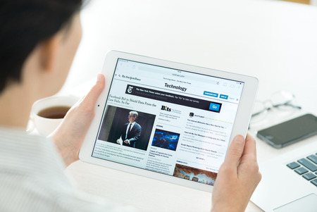 KIEV, UKRAINE - 27 juin 2014: Femme d'affaires de lire l'article en ligne du New York Times de nouvelles technologies sur un tout nouveau Apple iPad Air. Ce site est l'un des de l'Amérique site de nouvelles le plus populaire. Banque d'images - 29693045