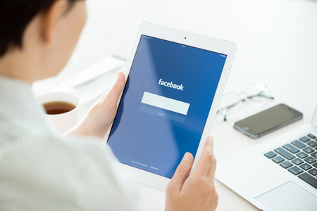 KIEV, UKRAINE - JUNE 27, 2014: Woman looking on Facebook application login page on modern white Apple iPad Air, which is designed and developed by Apple inc. and was released on November 1, 2013.