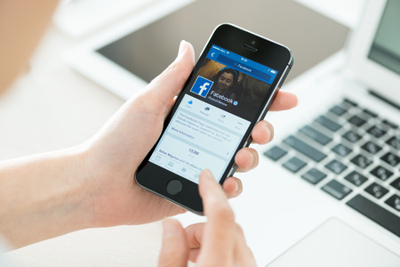 microblogging: KIEV, UKRAINE - JUNE 27, 2014: Person holding a brand new Apple iPhone 5S with Facebook profile on the screen. Facebook is a social media online service for microblogging and networking, founded in February 4, 2004.