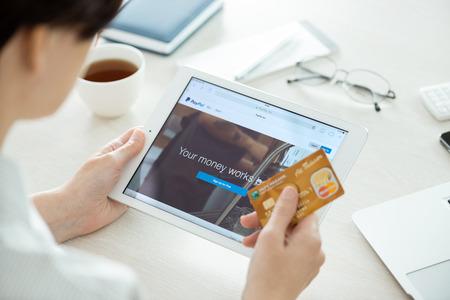 transaction: KIEV, Oekraïne - 27 juni 2014: Persoon met creditcard in de hand te kijken op een gloednieuwe Apple iPad Air met Paypal website op een scherm. Paypal is de wereldwijde e-commerce business service waarmee betalingen en geldtransacties via internet, opgericht in juni, Redactioneel