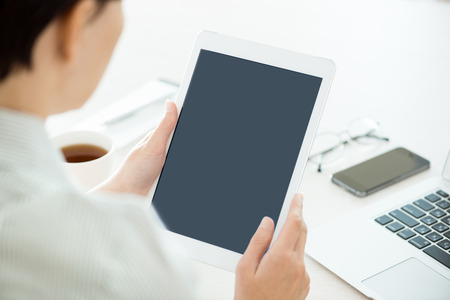 Business person holding modern digital tablet and looking on a blank screen  Stylish modern office workplace on a background  photo