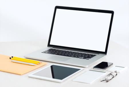 articulos oficina: Lugar de trabajo moderno de la oficina con el ordenador portátil metálico, tableta digital, teléfono móvil, papeles, bloc de notas y objetos de negocio y otros artículos extiende sobre una mesa. Aislado en el fondo blanco.