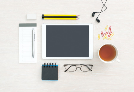 view from the above: Business workplace with modern blank digital tablet, office supplies and objects for daily routine, regular items on a desk background. Top view. Stock Photo