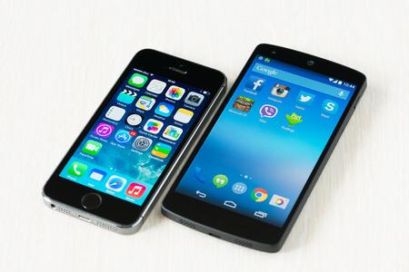 Kiev, Ukraine - le 29 Septembre, 2014: Gros plan de la marque nouvel iPhone d'Apple et Google Nexus 5S 5 smartphones se trouvant sur un bureau.