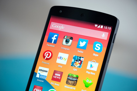 android: Kiev, Ukraine - September 22, 2014: Close-up shot of brand new Google Nexus 5, powered by Android 4.4 version, with various mobile applications on a screen.