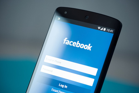 Kiev, Ukraine - September 22, 2014: Close-up photo of brand new Google Nexus 5, powered by Android 4.4 version, with Facebook login account page on a screen.