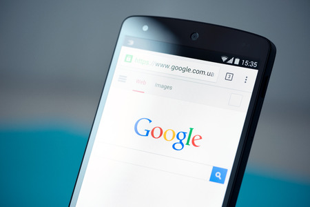 Kiev, Ukraine - September 22, 2014: Closeup photo of brand new Google Nexus 5, powered by Android 4.4 version, with Google search webpage in Chrome browser on a screen.