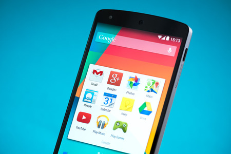 google play: Kiev, Ukraine - September 22, 2014: Close-up shot of brand new Google Nexus 5, powered by Android 4.4 version, manufactured by LG Electronics. Isolated on blue background.