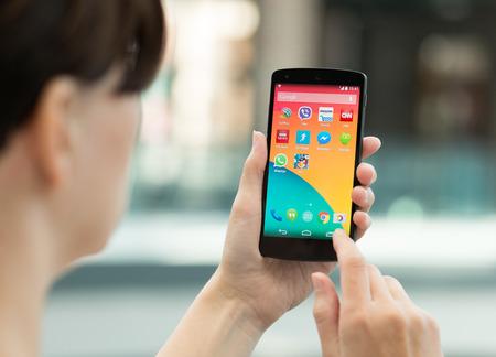 키예프, 우크라이나 - 2014년 9월 14일는 : 여자는 야외에서 새로운 구글 넥서스 5를 사용. 구글 넥서스 5는 LG 전자에서 제조 한 안드로이드 4.4 버전에 의