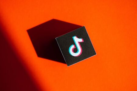 Kyiv, Ukraine - September 5, 2019: A shot from above of paper cube with the printed logotype of the TikTok application, that placed on a orange background.