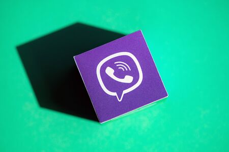 Kyiv, Ukraine - September 5, 2019: A shot from above of paper cube with the printed logotype of the Viber application, that placed on a green background. Redakční