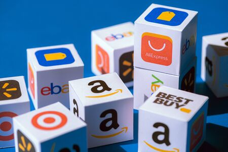 Kyiv, Ukraine - September 10, 2019: A paper cubes collection with printed logos of eCommerce corporations and online retail stores, such as AliExpress, WallMart, eBay, Amazon, and others. Redakční