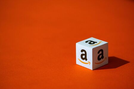 Kyiv, Ukraine - September 10, 2019: A shot of paper cube with the printed logotype of the Amazon company, that placed on an orange background.