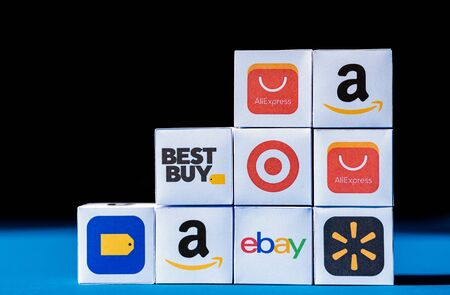 Kyiv, Ukraine - September 10, 2019: A wall from paper boxes with printed logos of eCommerce corporations and online retail stores, such as eBay, AliExpress, Best Buy, Amazon, and others.