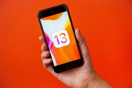 Kyiv, Ukraine - September 19, 2019: Studio shot of hand holding Apple iPhone 8 with an abstract wallpaper image about the release of the new iOS 13 version that Apple Inc. released today.