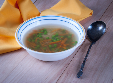 Bowl of Warm Soup with Green Peas, Carrot and Rice.
