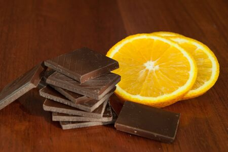 Chocolate, nuts, berries and orange on glossy wooden background
