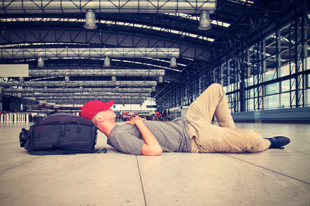 baggage: Tired man lying at the airport with passport in hand