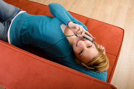 Young woman using a cell phone while lying on a red couch photo