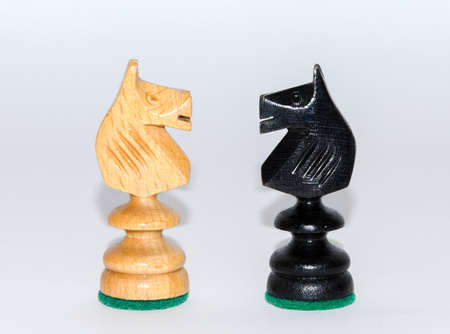 adverse: Face to face - two knights, wooden chess pieces, white background