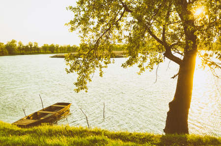 backwater: summer landscape - wooden boat, backwater, tree and sunset. Stock Photo