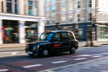 A picture of taxi or cab captured in motion or in panning technique in daylight in London, UK. Concept of hurry and speed