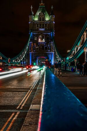 Long exposure night shot in portrait orientation of the Tower Bridge in London with blurred tourist faces