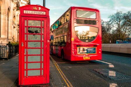 Eine ikonische rote Telefonzelle und ein roter fahrender Bus in London, Vereinigtes Königreich Standard-Bild