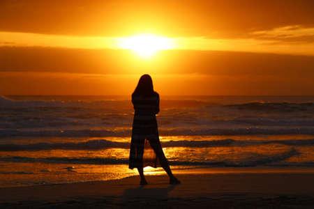 Silhouette di una donna che guarda l'alba sulla spiaggia di Surfers Paradise, Gold Coast, Australia.