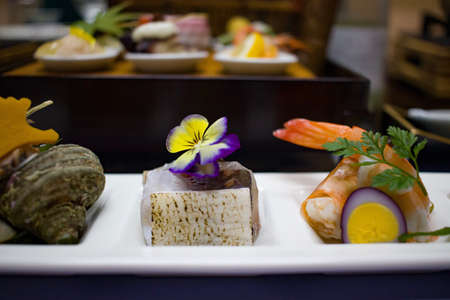 Authentic Japanese food served in small portions with floral garnish. Stock Photo