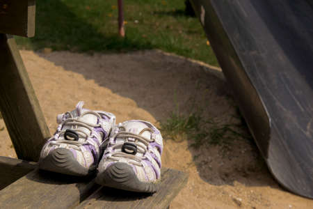 forgot: Old worn sandals left on a bench at the playground Stock Photo
