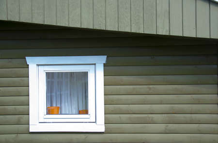 house gable: A square white window on a green wooden house with visible gable overhang