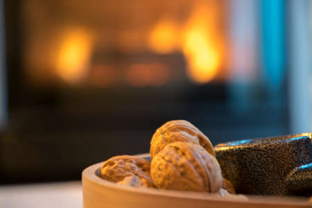 Walnuts in a wooden bowl on a white table with a cozy lit fireplace in the background