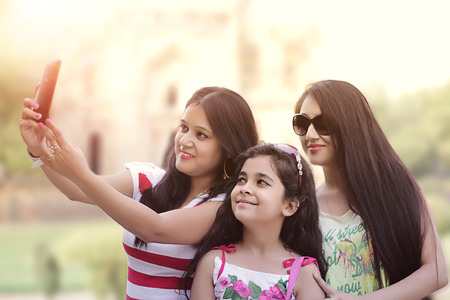 indian subcontinent ethnicity: Indian girls taking a selfie with mobile phone in park. Stock Photo