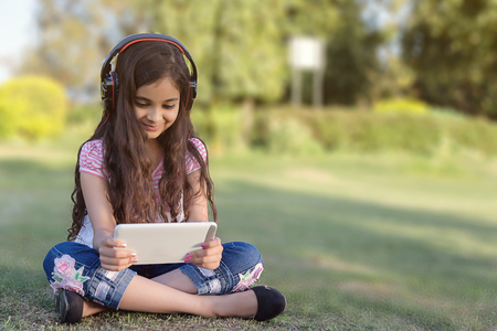 Girl Playing Tablet Wearing Wireless Headphones. Ten Years Old Girl Listen Music and Playing Games on the Tablet Device. vertical composition.