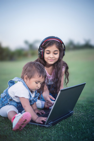multi age: Beautiful little girls sitting in the grass in a park and using laptop. Stock Photo
