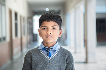 Closeup portrait of smiling 6-7 years Indian kid, standing straight at school campus in school uniform and looking at camera Stock Photo