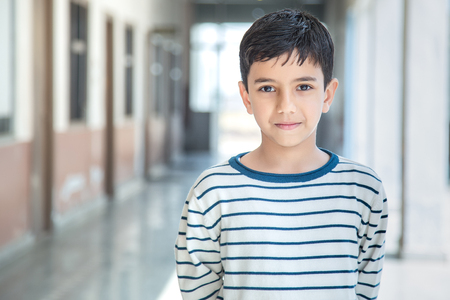 Portrait of smiling 6-7 years Indian kid, standing straight at school campus in school uniform and looking at camera Stock Photo