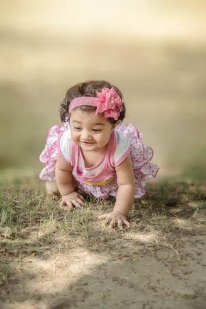 Selective focus of Happy 6 month IndianAsian little kid wearing pink dress crawling on the grass and playing. shallow depth of field. Stock Photo