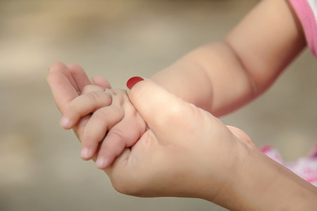 mother holding her baby hand close-up. Stock Photo - 104676956