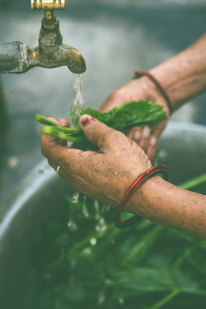 Women washing vegetable under tap water outside.
