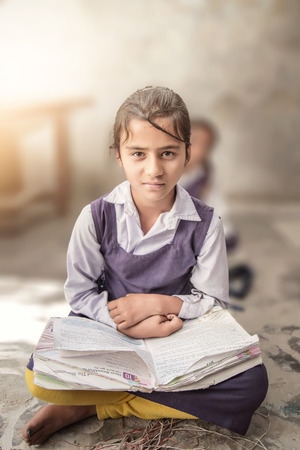 Girl sitting on the floor of her government primary school in uniform along with some of her class mates sitting behind her. Selective focus, shallow depth of field.