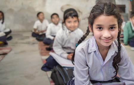 Fille assise sur le sol de son école primaire gouvernementale en uniforme avec certains de ses camarades de classe assis derrière elle. Mise au point sélective, faible profondeur de champ. Banque d'images