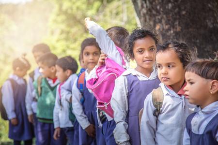 Village elementary school kids forming line for morning prayer. different age group children wearing school uniform.