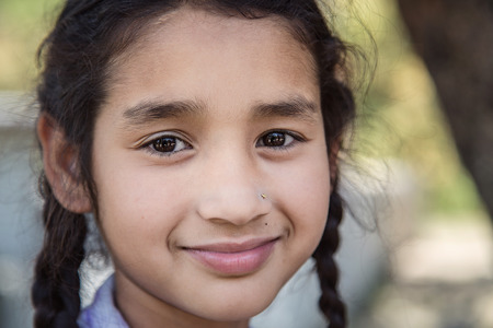 Portrait of smiling elementary IndianAsian school girl looking at camera.
